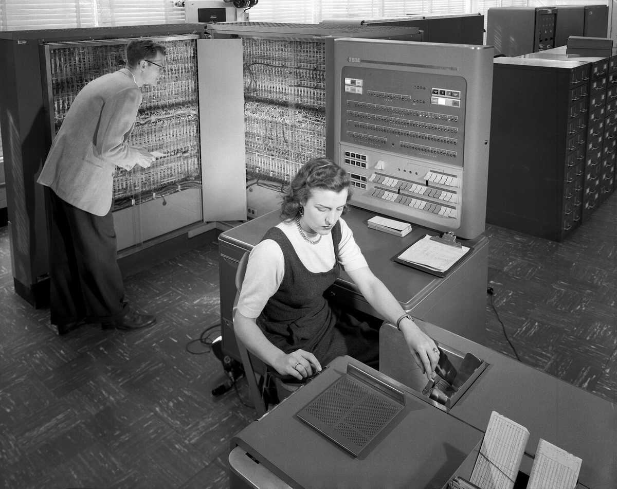 Two people working on old IBM 704 computer at NASA in 1957